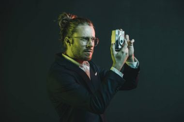 man in tuxedo taking photo on camera