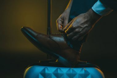 stylish man tying shoelaces on suitcase