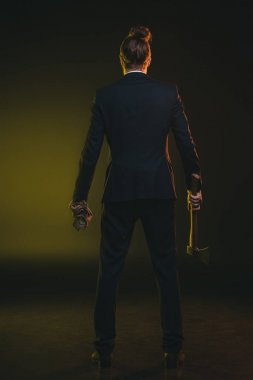 man in tuxedo holding ax and money