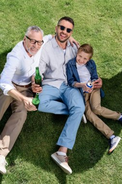 grandfather, father and son hugging on grass