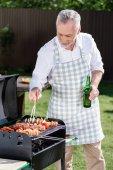 Grauhaariger Mann bereitet Grill vor