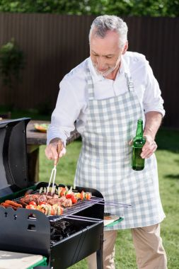 Grey haired man preparing barbecue