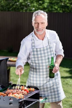 Smiling grey haired man drinking beer from bottle during preparation of barbecue on grill stock vector