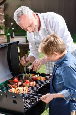 Grey haired grandfather with his grandson preparing meat and vegetables on grill outdoors stock vector