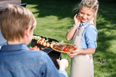 kids preparing meat and vegetables on grill