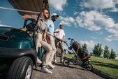 men standing near golf cart