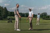 Lächelnde Freunde beim Golfspielen