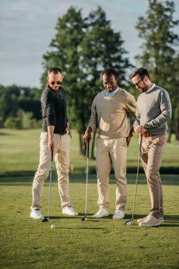 multiethnic friends playing golf