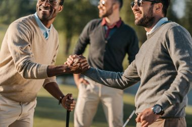 Happy multicultural friends shaking hands while playing golf on golf course stock vector