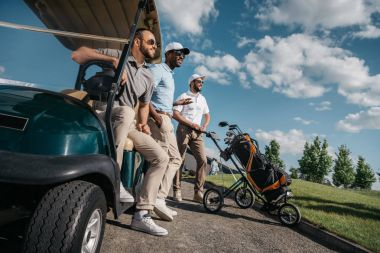men standing near golf cart