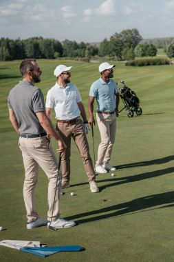 Multiethnic golf players looking away