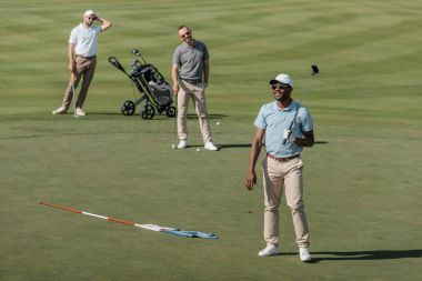 Sportsmen standing with golf clubs on pitch