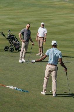 Multiethnic golfers talking during game