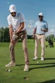 golfista uvedení míč do díry