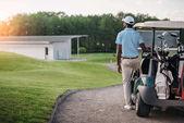 golfista stojící poblíž golfový vozík