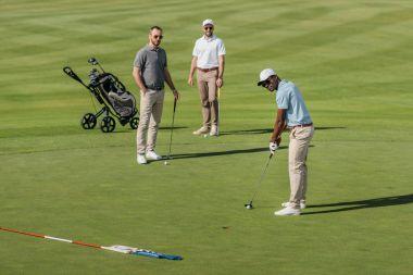 african american golfer take a shot