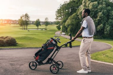 Man with golf clubs in bag