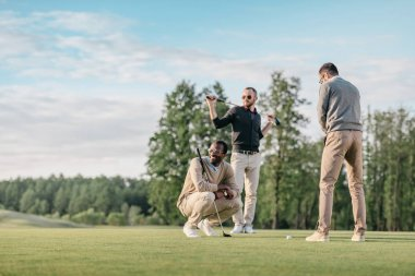 multiethnic friends playing golf