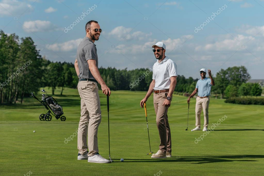 smiling friends playing golf