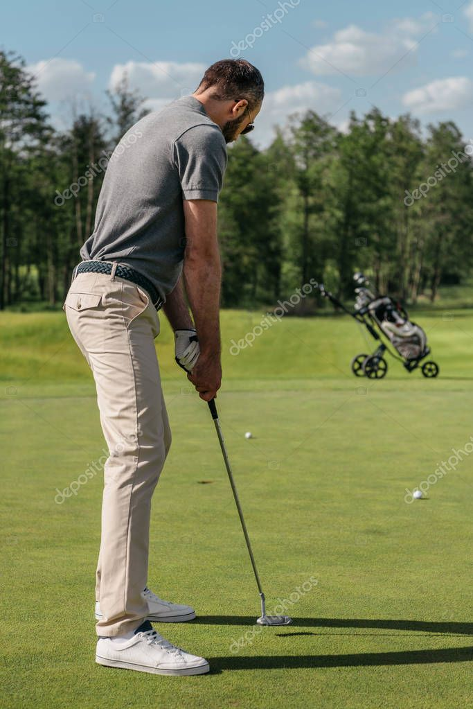 young casual man playing golf