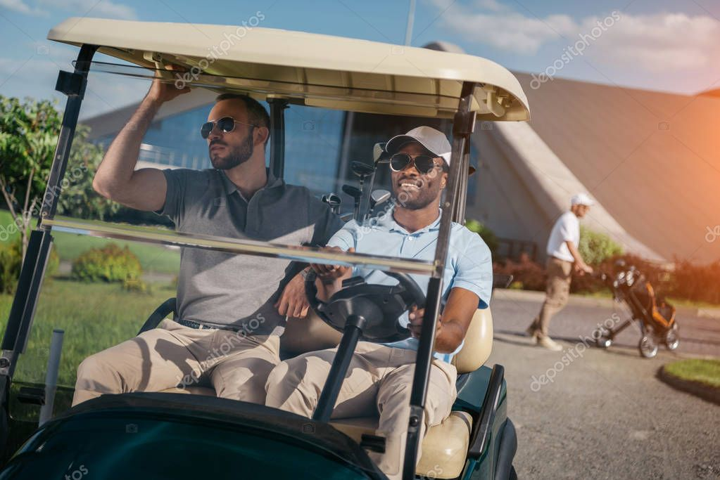 men riding golf cart