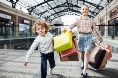 happy children holding shopping bags