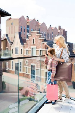 Daughter and mother holding shopping bags