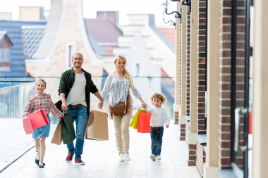family with shopping bags holding hands