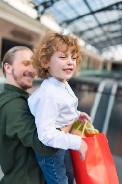 father holding son with shopping bags