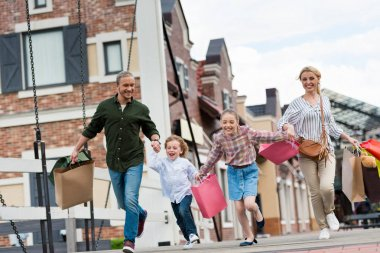 Family running with shopping bags on street