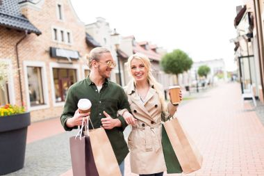 couple walking with shopping bags on street