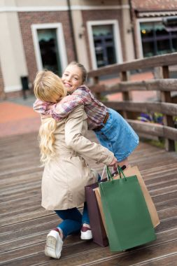 Mother with daughter with shopping bags