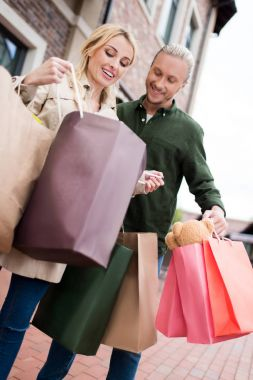 couple looking into shopping bags on street