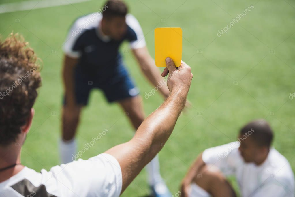 referee showing yellow card