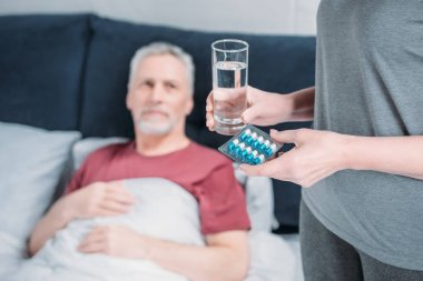 woman giving medicines to husband