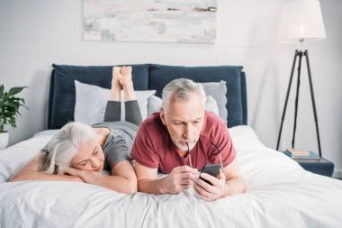 couple with smartphone in bed