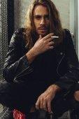 Stílusos hosszú hajú férfi cigarettával
