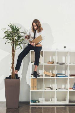 Businessman with folder sitting on bookshelf