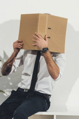Businessman hiding face with folder