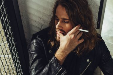 Stylish long haired man with cigarette