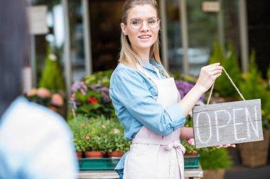 florist holding open sign