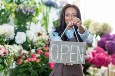 florist holding open sign