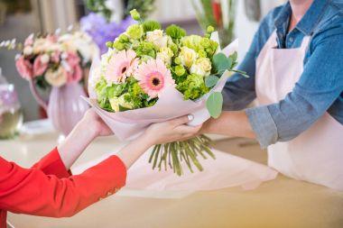 florist giving bouquet to client