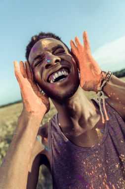 Close-up portrait of happy african american man with colorful paint of face laughing with closed eyes at holi festival stock vector