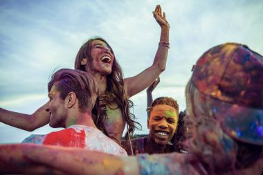 Cheerful young multiethnic friends with colorful paint on clothes and bodies having fun together at holi festival stock vector