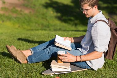 man reading book in park