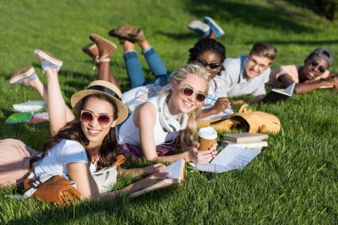 multiethnic students reading books in park