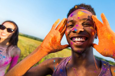 Close-up portrait of happy african american man with colorful paint of face smiling and looking away at holi festival stock vector