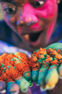 Close-up view of shocked african american girl blowing colorful powder from palms at holi festival stock vector