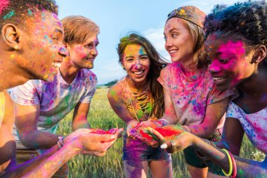 Cheerful young multiethnic friends holding colorful paint in hands at holi festival stock vector